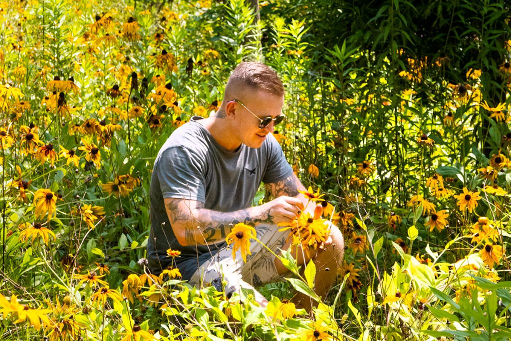 Chef/forager Elijah Holland picking echinacea at Gucun Park. Photo by Rachel Gouk