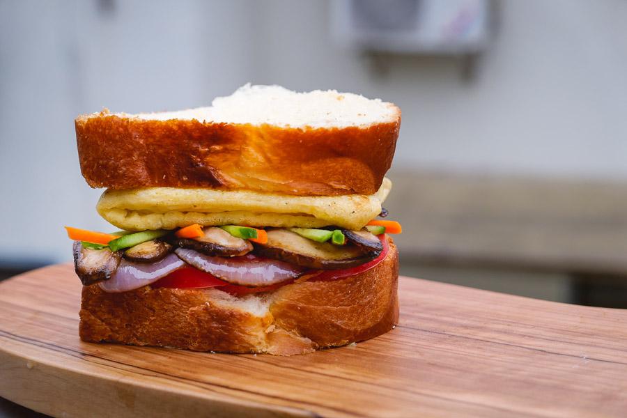 Fully loaded plant-based sandwich for vegans. Easy recipes with plant-based egg alternative JUST Egg. Photos by Rachel Gouk @ Nomfluence.